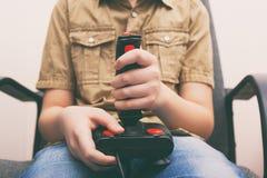 Muchacho joven que juega al videojuego con una palanca de mando retra fotografía de archivo