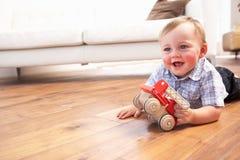Muchacho joven que juega con el coche de madera del juguete en el país Foto de archivo libre de regalías