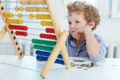 Muchacho joven que juega con el contador y las monedas Imagenes de archivo
