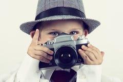 Muchacho joven que juega con la cámara vieja para ser un fotógrafo Foto de archivo libre de regalías