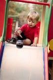 Muchacho joven que juega con Toy Car en diapositiva Imágenes de archivo libres de regalías