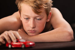 Muchacho joven que juega con un coche modelo Fotografía de archivo libre de regalías