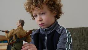 Muchacho joven que juega con una muñeca del hombre metrajes