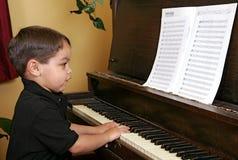 Muchacho joven que juega el piano fotos de archivo
