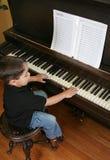 Muchacho joven que juega el piano imagenes de archivo