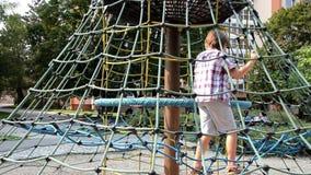 Muchacho joven que juega en cuerdas en un parque almacen de video