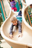 Muchacho joven que juega en diapositiva en patio Foto de archivo libre de regalías