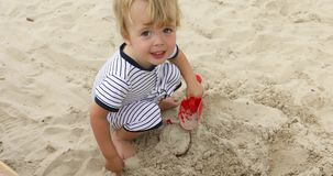 Muchacho joven que juega en la arena metrajes