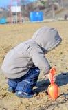 Muchacho joven que juega en la arena de la playa Imagenes de archivo