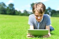 Muchacho joven que juega en la PC de la tableta Imagenes de archivo