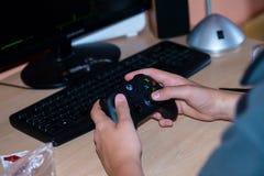 Muchacho joven que juega en Xbox a un videojuego en de computadora personal imagen de archivo libre de regalías