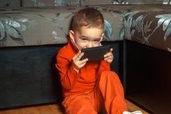Muchacho joven que juega a juegos móviles Fotos de archivo
