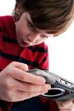 Muchacho joven que juega la consola handheld del juego Foto de archivo libre de regalías