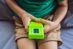 Muchacho joven que juega la videoconsola port?til de la escuela vieja, juguete retro electr?nico del bolsillo con la exhibici?n m imagen de archivo