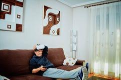 Muchacho joven que juega a los videojuegos con los vidrios 3d imagen de archivo libre de regalías