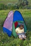 Muchacho joven que juega usando una tapa del regazo Foto de archivo