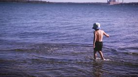 Muchacho joven que lanza una pequeña losa del hormigón en el agua de superficie y que la recupera para hacerla otra vez Diversión almacen de video