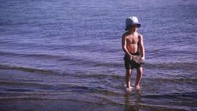 Muchacho joven que lanza una peque?a losa del hormig?n en el agua de superficie y que la recupera para hacerla otra vez Diversi?n almacen de metraje de vídeo