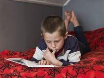 Muchacho joven que lee un libro Imagen de archivo libre de regalías