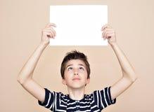 Muchacho joven que lleva a cabo al tablero blanco en blanco Fotografía de archivo libre de regalías