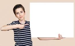 Muchacho joven que lleva a cabo al tablero blanco en blanco Fotografía de archivo