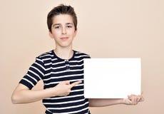 Muchacho joven que lleva a cabo al tablero blanco en blanco Fotos de archivo