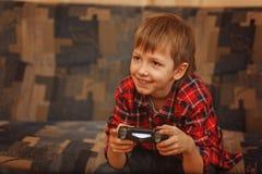 Muchacho joven que lleva a cabo el gamepad y que juega a los videojuegos Fotografía de archivo libre de regalías