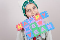 Muchacho joven que lleva a cabo en sus dientes una muestra de la Feliz Año Nuevo Imagenes de archivo