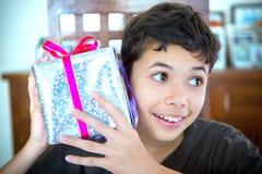 Muchacho joven que lleva a cabo para arriba envuelto un regalo de Navidad Fotografía de archivo