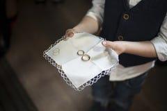 Muchacho joven que lleva a cabo un anillo de oro en la placa Imagen de archivo