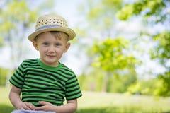 Muchacho joven que lleva un sombrero de ala en el parque Fotos de archivo