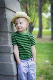 Muchacho joven que lleva un sombrero de ala en el parque Imagenes de archivo