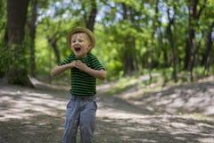 Muchacho joven que lleva un sombrero de ala en el parque Imagen de archivo