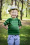 Muchacho joven que lleva un sombrero de ala en el parque Fotos de archivo libres de regalías