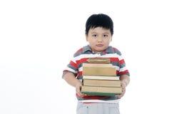 Muchacho joven que lleva una pila de libros Fotografía de archivo libre de regalías