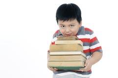Muchacho joven que lleva una pila pesada de libros Imagen de archivo libre de regalías