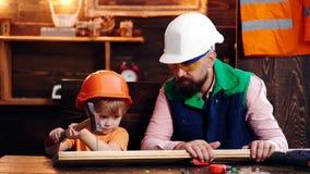 Muchacho joven que martilla el clavo en tabl?n de madera Muchacho ocupado en el casco protector que aprende utilizar el martillo  metrajes