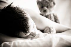 Muchacho joven que miente en cama con Teddy Bear Fotografía de archivo libre de regalías