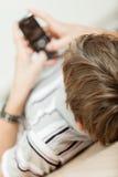 Muchacho joven que miente en el piso con su móvil Fotos de archivo libres de regalías