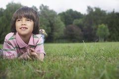Muchacho joven que miente en prado Foto de archivo