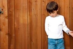Muchacho joven que mira abajo en la cerca de madera Fotos de archivo libres de regalías