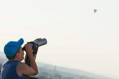 Muchacho joven que mira el baloon del vuelo a través del telescopio Fotografía de archivo