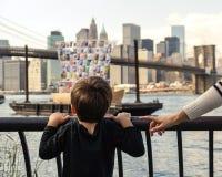 Muchacho joven que mira el barco con el horizonte de Manhattan el fondo Foto de archivo libre de regalías