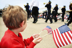 Muchacho joven que mira el desfile del Memorial Day Imagen de archivo