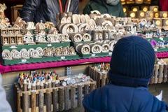 Muchacho joven que mira en la decoración hecha a mano de la Navidad fuera de la madera en una cabina del mercado de la Navidad en imagenes de archivo