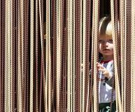 Muchacho joven que mira hacia fuera de detrás la cortina Imagenes de archivo