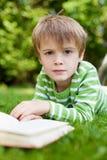 Muchacho joven que mira para arriba de leer un libro Imagenes de archivo