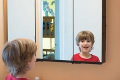 Muchacho joven que mira se en espejo Foto de archivo