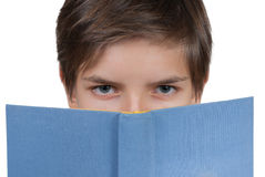 Muchacho joven que mira a través detrás de un libro azul Fotografía de archivo libre de regalías