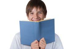 Muchacho joven que mira a través detrás de un libro azul Foto de archivo libre de regalías